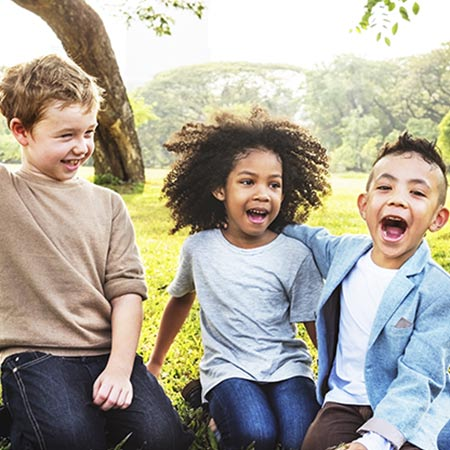 Three children laughing in a field