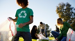 college students recycling plastic on grass