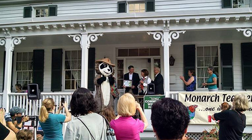 People gathered for Community Wildlife Habitat certification celebration on porch of a white house