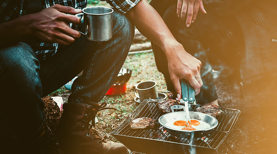 people cooking eggs at a campsite