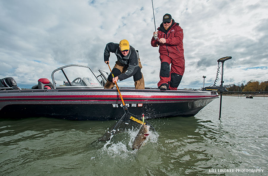 Anglers netting a smallmouth bass