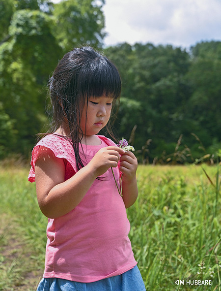 Child (female) plays with wildflowers at the Reflection Riding Nature Center summer camp