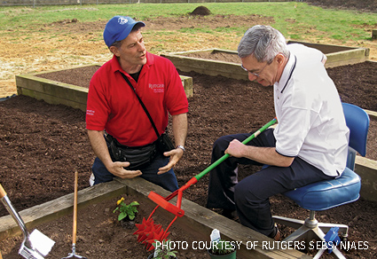 Therapist Joel Flagler demonstrates the use of adjustable planting tools to a recovering stroke victim