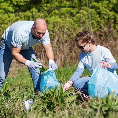 A man and a woman cleaning up trash in a field