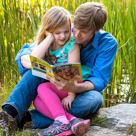 Father reading Ranger Rick magazine to daughter