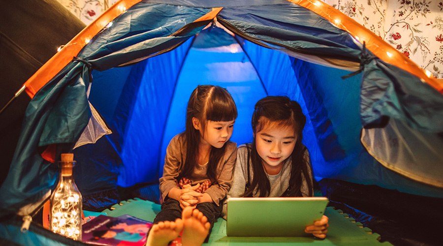 two young girls camping in a tent